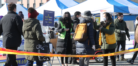 Customers get checked before entering a traditional market in Seongnam, Gyeonggi, on Tuesday. The inflow of people at traditional markets has risen ahead of the Lunar New Year holidays, which kicks off on Thursday. [YONHAP]