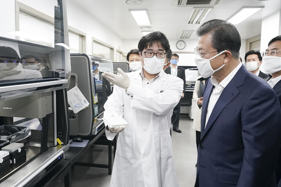 President Moon Jae-in, right, visits Seegene's research center in Songpa on March 25, 2020. [YONHAP]