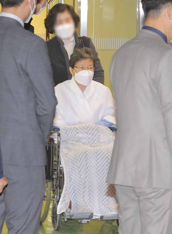 Former President Park Geun-hye is discharged from Seoul St. Mary's Hospital in Seocho District, southern Seoul, in a wheelchair on Tuesday. Park was sent back to the Seoul Detention Center to serve her jail time. Park had been quarantined for two weeks in the hospital after she was suspected to have had close contact with a confirmed Covid-19 patient in the Seoul Detention Center. [NEWS1]