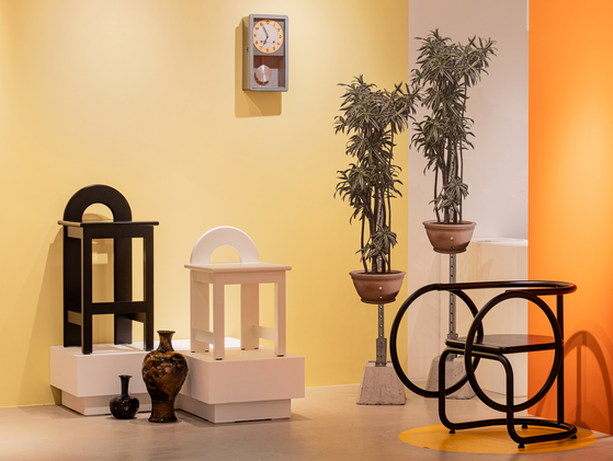 Artist Seol Su-bin's chair and Um Ah-rong's plant installations are positioned underneath a clock hanging on a yellow wall. [CHOI YONG-JOON]