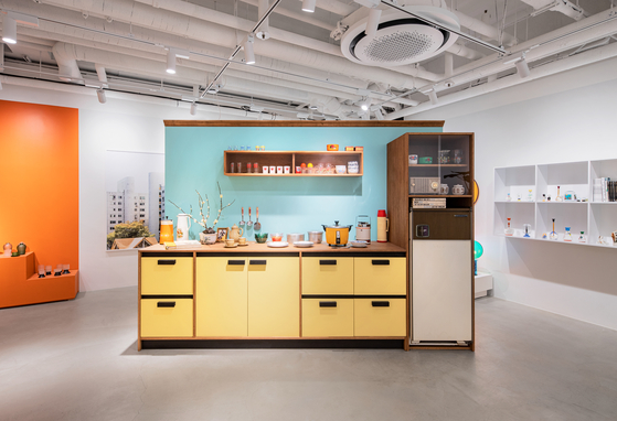 A large lemon-colored kitchen unit at the center of the exhibition is a recreation of a vintage ad. [CHOI YONG-JOON]