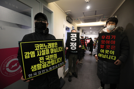 Coin noraebang owners demonstrates against the government business hours restriction at a coin noraebang in Seodaemnu, Seoul on Tuesday. [NEWS1]