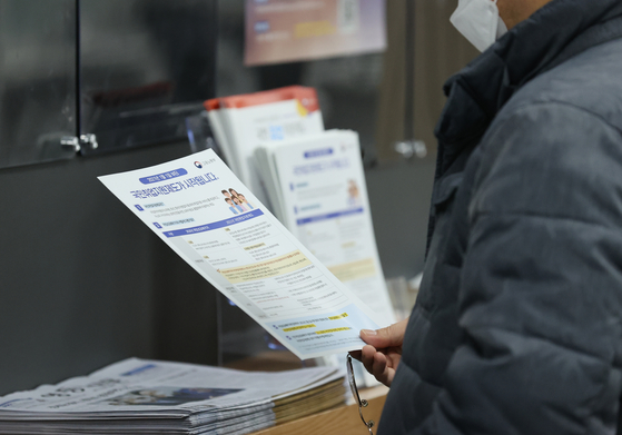 A job seeker looking at a booklet introducig government job programs at a center in Yeongdeungpo District on Feb. 3. The Statistics Korea on Feb. 10 announced that Janaury reported the worst job losses since the IMF crisis. [YONHAP]