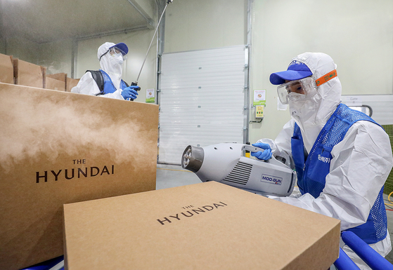 Workers from Hyundai Department Store disinfect packages as part of preventive measures against Covid-19. [HYUNDAI DEPARTMENT STORE]