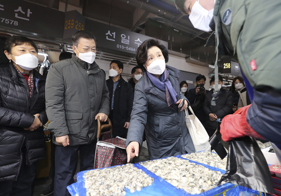 President Moon Jae-in and First Lady Kim Jung-sook buy fishery products for the Lunar New Year holiday at an outdoor fish market in Incheon on Wednesday. [JOINT PRESS CORPS]