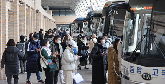 People wearing masks board buses at the Express Bus Terminal in Seocho District, southern Seoul, on Wednesday, to spend the Lunar New Year holidays with their relatives. The number of people traveling is expected to be much less this Lunar New Year because of the Covid-19 pandemic. [YONHAP]