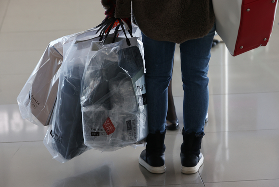 A passenger leaving for a no-destination flight on Jeju Air heads to the departure gate with purchased duty-free items at Incheon International Airport on Dec. 12, 2020. [YONHAP]