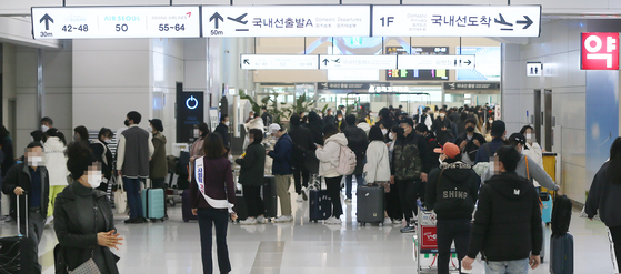 A departure terminal for domestic flights at Jeju International Airport is packed with tourists on Sunday. [YONHAP]
