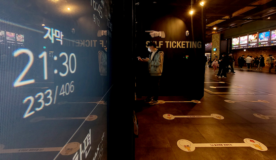 A ticket booth at a theater in Seoul Sunday displays a movie to be screened at 9:30 p.m. Monday after the government announced an easing of social distancing measures to lift the operating hour restrictions of many businesses nationwide. [YONHAP]