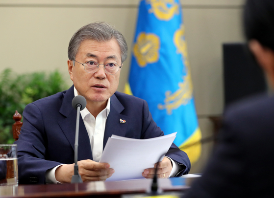 In this file photo, President Moon Jae-in receives a briefing from Justice Minister Park Sang-ki and Interior and Safety Minister Kim Boo-kyum about a series of sex, drug and police protection scandals surrounding the country's celebrities and top politicians and orders thorough investigations. One of the scandals involved former Vice Minister of Justice Kim Hak-eui of the previous administration. [YONHAP]