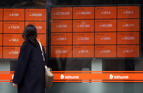 A passerby looks at cryptocurrency prices displayed through a screen operated by local crytocurrency exchange Bithumb in Gangnam, southern Seoul, on Monday. [YONHAP]