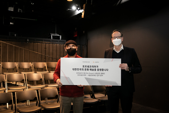 Porsche Korea CEO Holger Gerrmann, right, and Kim Jong-hwi, CEO of SFAC pose for a photo at a theater in Jung District, central Seoul on Monday. [PORSCHE KOREA]