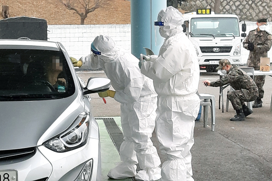 Quarantine officials administer Covid-19 tests for military officers at a drive-through testing station at the Defense Ministry in Yongsan District, central Seoul, on Tuesday after the first coronavirus case at the Joint Chiefs of Staff (JCS) was reported earlier in the day. [YONHAP]