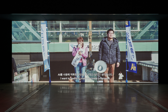 Jung Yoon-suk's documentary ″Tomorrow″ also follows the members of the AI Party who tried to get votes by promoting the usage of artificial intelligence as its decision maker. [MMCA]