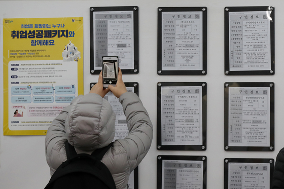 A job seeker takes a photo of an employment posting at the Seoul Western Employment and Welfare Center in Mapo District on Feb. 10, 2020.  [NEWS1]