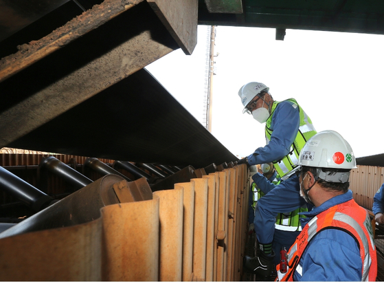 Posco Chairman Choi Jeong-woo, left, checks a conveyor belt on Wednesday at the company's steel mill in Pohang where a contractor recently died due to an accident. [POSCO]