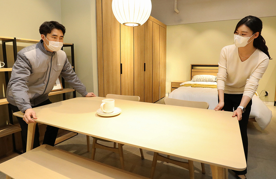 Hyundai Livart workers deliver a table. [HYUNDAI LIVART]