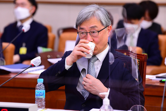 Choe Jae-hyeong, chairman of the Board of Audit and Inspection, drinks water during the Legislation and Judiciary Committee meeting at the National Assembly on Thursday. [YONHAP]
