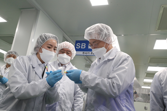 "President Moon Jae-in, right, examines ""low dead space (LDS)"" syringes designed to reduce the dead space between the needle and the body, to be used in Covid-19 vaccinations to minimize waste in dosages, at PoongLim Pharmatech in Gunsan, North Jeolla Thursday. [JOINT PRESS CORPS]"