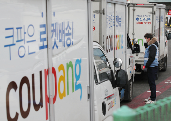 A Coupang worker talks with the company's courier in Seoul on Tuesday. Coupang said Thursday that it will distribute shares worth 2 million won ($1,800) to workers working as of March 5 as it prepares for listing on the New York Stock Exchange. [YONHAP]