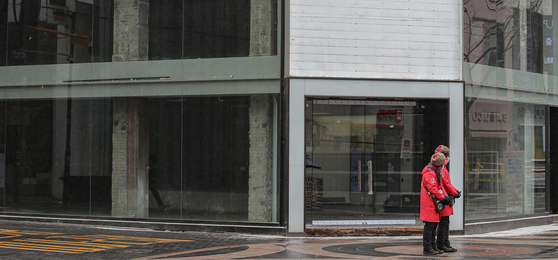 Seoul city government tour guides await tourists in front of an empty store in Meyong-dong on Feb. 16. Because of Covid-19, stores have shut down and people lost their jobs, increasing dependence on government support. [YONHAP]