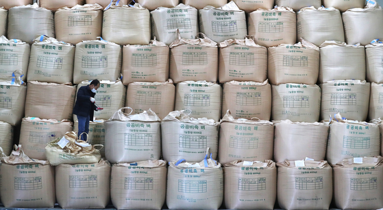 A man checks rice at a storage unit in Cheongju, North Chungcheong on Thursday afternoon. The government plans to supply 60,000 tons of rice to markets in order to stabilize the supply. [YONHAP]