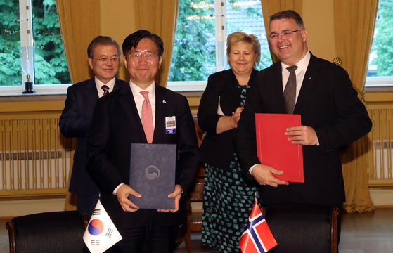 Sung Yun-mo, left, then-minister of trade, industry and energy of Korea, with Kjell-Børge Freiberg, Norwegian minister of petroleum and energy at the time, after signing an agreement on hydrogen economy and low-carbon technologies at the residence of Norwegian Prime Minister Erna Solberg on June 13, 2019. Behind them are Prime Minister Solberg, right, with Korea's President Moon Jae-in, left. [JOINT PRESS CORPS OF THE BLUE HOUSE]