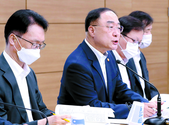 Finance Minister Hong Nam-ki, second from left, announces the government's tax reform plans during a briefing held at the Sejong Government Complex in July last year. [YONHAP]