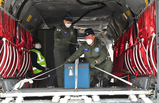 Military officials secure a container on the Air Force's Boeing CH-47 Chinook helicopter at Icheon, Gyeonggi, Friday, taking part in a governmental mock drill running through the distribution of Covid-19 vaccines to remote areas without access to airports. [JOINT PRESS CORPS]