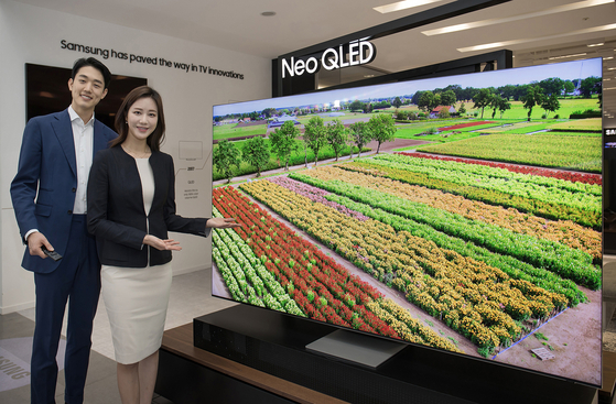 """Models introduce Samsung Electronics' new Neo QLED TV at Samsung Digital City in Suwon, Gyeonggi, on Monday. According to the company, Video, a German audio and video magazine, described the Neo QLED as the """"Best TV of All Time."""" [YONHAP]"""