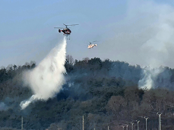 Firefighting helicopters extinguish flames at a wildfire site in Andong, North Gyeongsang on Monday. The fire forced 108 residents in the area to evacuate on Sunday afternoon and evening. [YONHAP]