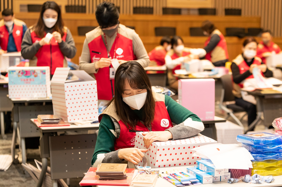 Lotte World employees wrap gifts for underprivileged young people ahead of the Lunar New Year holiday. [LOTTE GROUP]