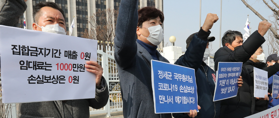 Small shop owners, including those who own indoor gyms, demand the government create a measure that would compensate for losses incurred due to the strict social distancing rather than a universal emergency relief grant in front of the government complex in Seoul on Feb. 22. [YONHAP]