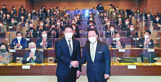 SK Group Chairman Chey Tae-won, left, shakes hand with Park Yong-maan, Korea Chamber of Commerce and Industry (KCCI) chairman, at the KCCI headquarters in Seoul on Tuesday. Chey has been voted as the business group's new chairman, taking over for Park. The term for the chairman is three years. However, Park has served in the position since 2013. [YONHAP]