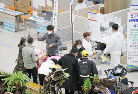 Travelers go through screenings at Incheon International Airport as all visitors to the country, including Koreans, are required to show negative polymerase chain reaction (PCR) tests starting Wednesday. [YONHAP]