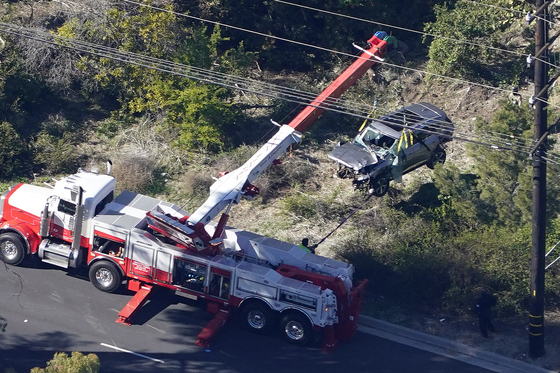 Workers move a vehicle after a rollover accident involving golfer Tiger Woods on Tuesday in Rancho Palos Verdes, Calif., a suburb of Los Angeles.. Woods suffered leg injuries in the one-car accident and was undergoing surgery, authorities and his manager said. [AP]