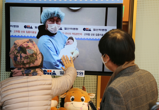 Grandparents welcome a grandchild born on the first day of 2021 via a monitor, because of social distancing regulations, in a hospital in Goyang, Gyeonggi. [YONHAP]