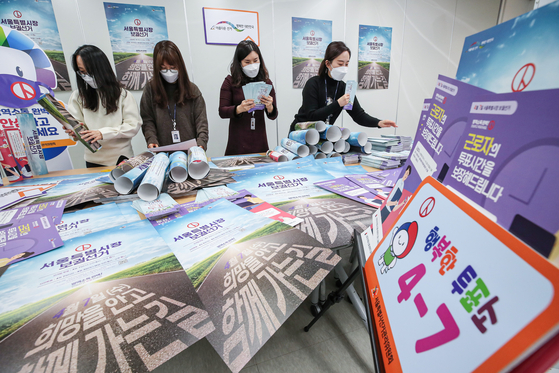 Officials from the Seoul branch of the National Election Commission on Wednesday examine posters to encourage voters to cast their ballots in the by-election for Seoul mayor on April 7. [YONHAP]