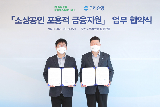 Woori Bank CEO Kwon Kwang-seok, right, and Naver Financial CEO Choi In-hyuk pose for a photo after inking a partnership to offer specialized loans for small online sellers on Wednesday at Woori Bank's main branch in Jung District, central Seoul. [NAVER FINANCIAL]