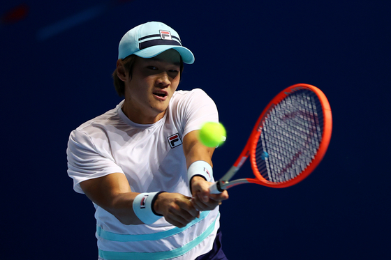 Kwon Soon-woo plays a backhand in his men's singles first round match against Thai-Son Kwiatkowski of the United States at the Singapore Tennis Open on Wednesday in Singapore. [GETTY IMAGES]