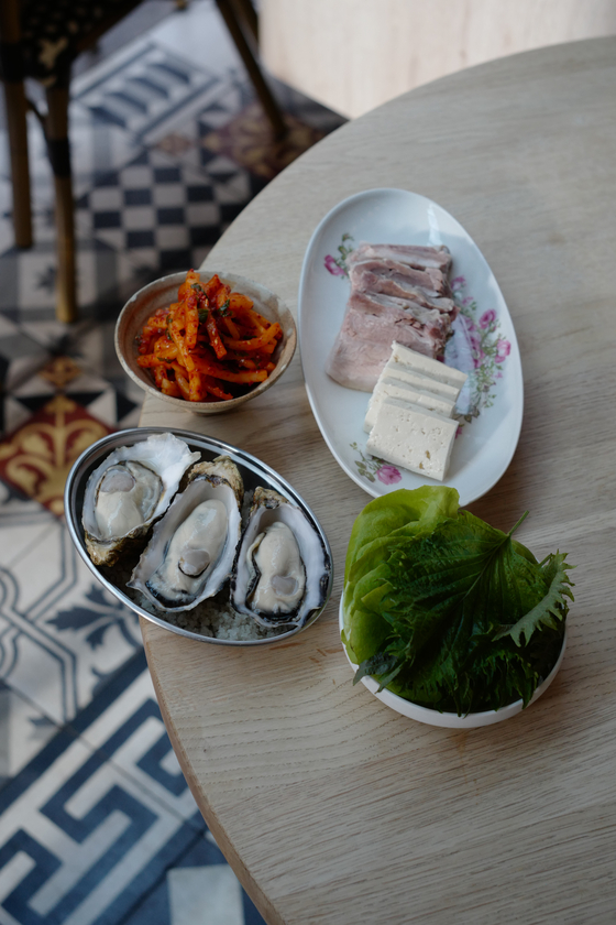 Bossam, or steamed pork, comes with many different sides to eat together, such as oyster, and radish seasoned with gochugaru. [AGENCE NEROLI]