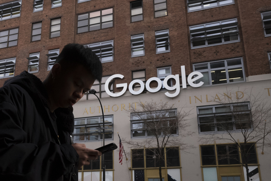 In this Dec. 17, 2018, file photo a man using a mobile phone walks past Google offices in New York. [AP/YONHAP]