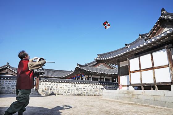 Rhee flies a bangpae kite in Namsangol Hanok Village. [PARK SANG-MOON]
