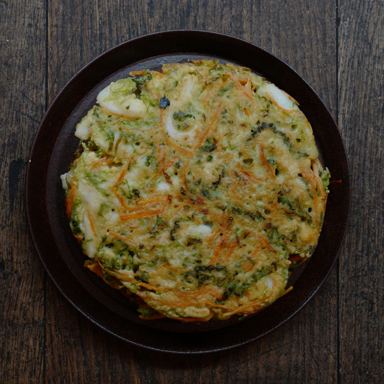 Haemul Pajeon, a Korean style savory pancake made mostly with scallions accompanied by all kinds of seafood, is widely loved for its crunchy texture that embraces the softer inside. Many Koreans usualy pair the dish with makgeolli, fermented rice drinks. The combnation of the two are most sought after on a rainy day. [AGENCE NEROLI]