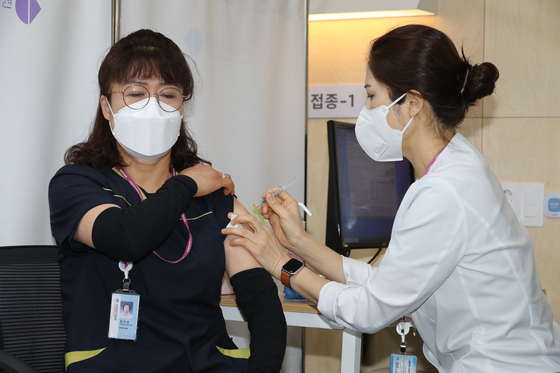 Jeong Mi-kyeong, left, a 51-year-old sanitation worker at the National Medical Center in central Seoul, is the recipient of the first Pfizer shot administered in the country at 9:04 a.m. Saturday. [YONHAP]