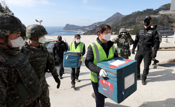 Local officials, escorted by the military and police, transfer AstraZeneca vaccines transported to a naval base on the remote Ulleung Island in the East Sea on the Air Force's Boeing CH-47 Chinook helicopter Sunday. [NEWS1]