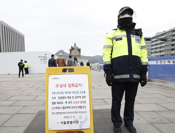 At Gwanghwamun Square in central Seoul on Sunday, a policeman stands next to a sign in which Seoul city government orders a ban on any rally in the downtown area, citing preventive measures to curb the spread of Covid-19 infection. Some conservative civic groups plan to stage anti-government rallies on Monday.  [NEWS1]