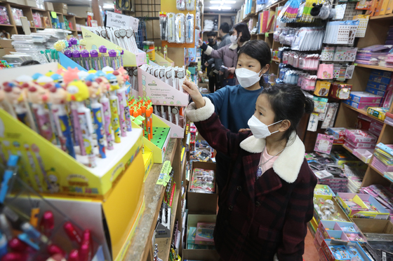 Students pick out school supplies a day ahead the new semester at a stationary store in Jongno District, central Seoul, on Monday. Under eased regulations, kindergarteners, first and second graders and high school seniors can go to school daily starting Tuesday. [NEWS1]