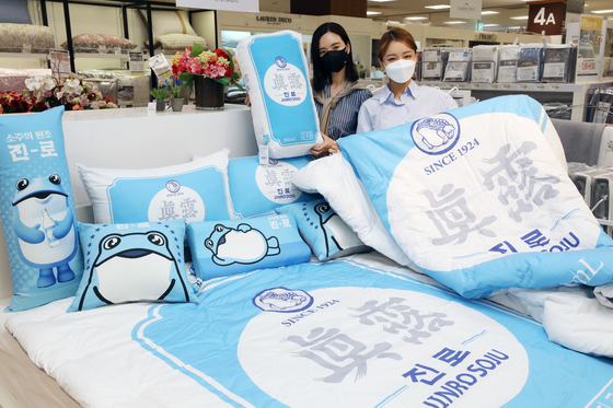 Models hold up bed sheets and pillows with the branding of Hite Jinro soju displayed at Emart's branch in Seongsu-dong, Seoul on Monday. The products are a collaboration with Nara Home Deco. Food and beverage companies have been increasingly collaborating with fashion companies. [EMART]