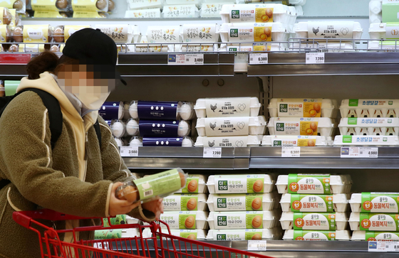 A customer picks up a carton of eggs at a major discount mart in Seoul on Monday. According to the Korea Institute for Animal Products Quality Evaluation, a flat with 30 eggs retails for an average 7,666 won ($6.90) as of Feb. 26. That's more than double the 3,015 won averaged in February last year. Food prices this month are expected to continue to rise amid the ongoing avian flu and the frequent snows. [YONHAP]